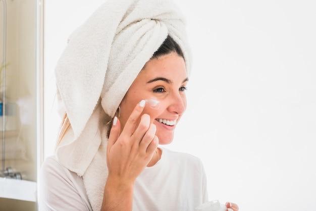 Retrato feliz de una mujer joven que aplica la crema en su cara Foto gratis