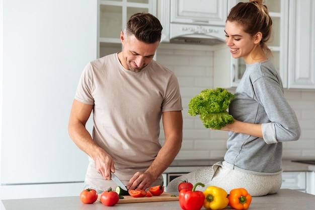 Retrato de una feliz pareja amorosa cocinar ensalada juntos Foto gratis