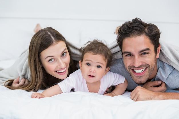 Retrato de la feliz pareja con bebé acostado en la cama | Foto ...