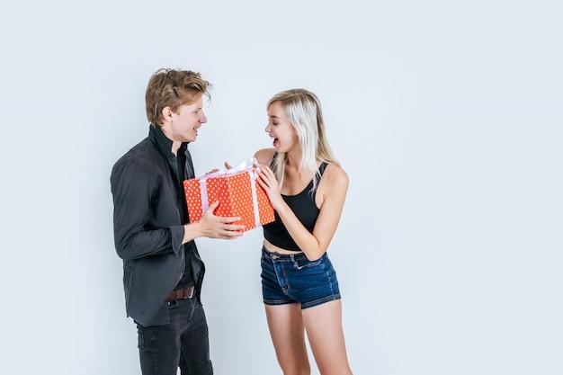 Retrato de feliz pareja joven amor juntos sorpresa con caja de regalo Foto gratis