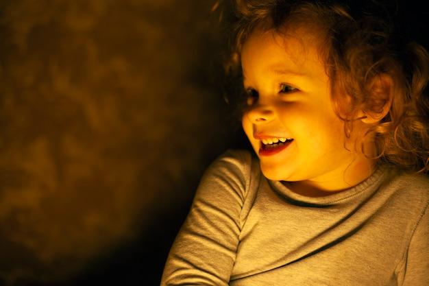 Retrato de una feliz y sonriente niña pelirroja en los cálidos rayos amarillos de una lámpara en el cuarto oscuro. Foto Premium