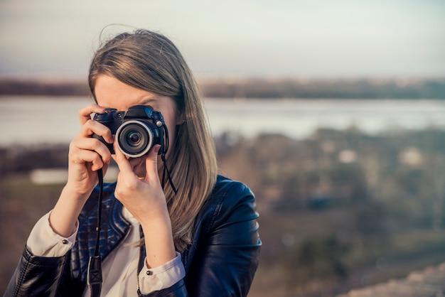 Retrato de un fotógrafo que cubre su cara con la cámara. ph Foto gratis