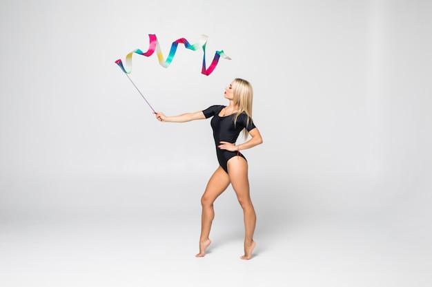 El retrato de gimnasta joven hermosa entrenamiento calilisthenics ejercicio con cinta. concepto de gimnasia de arte. Foto gratis