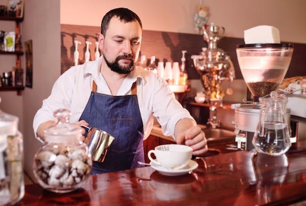 Retrato de un guapo barista barbudo preparando café en el fondo de una casa de café Foto Premium