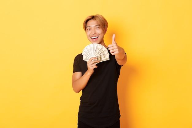 Retrato de guapo chico asiático sonriente seguro mostrando pulgar hacia arriba y sosteniendo dinero, garantizar algo, pared amarilla permanente Foto gratis