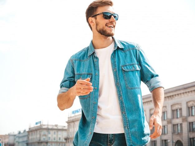 Retrato de guapo sonriente elegante hipster lumbersexual empresario modelo. hombre vestido con ropa de chaqueta de jeans. Foto gratis