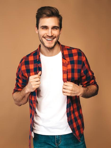 Retrato de guapo sonriente elegante joven modelo vestido con camisa a cuadros roja. hombre de moda posando Foto gratis