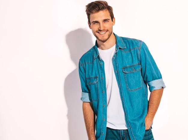 Retrato de guapo sonriente elegante joven modelo vestido con ropa de jeans. hombre de moda Foto gratis