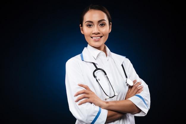 Retrato de hermosa enfermera morena aislada sobre negro Foto gratis