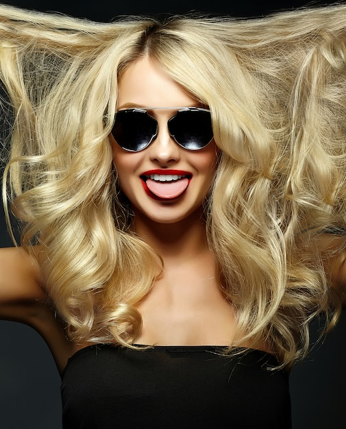 Retrato de hermosa feliz dulce linda mujer rubia sonriente niña con labios rojos y con el pelo rizado volando mostrando su lengua Foto gratis