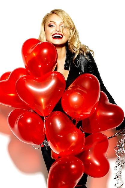 Retrato de hermosa feliz dulce sonriente mujer rubia niña sosteniendo en sus manos globos de corazón rojo en ropa casual hipster negro Foto gratis