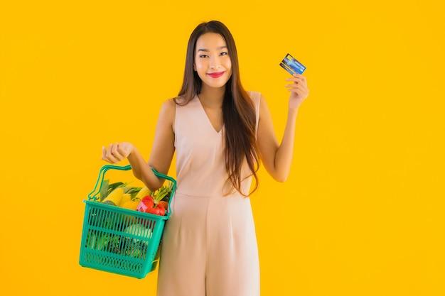 Retrato hermosa joven asiática con bolsa de compras de la cesta de la compra Foto gratis