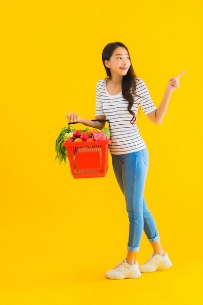 Retrato hermosa joven asiática con carrito de supermercado del supermercado en el centro comercial Foto gratis