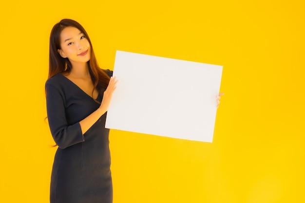 Retrato hermosa joven asiática con cartel vacío Foto gratis