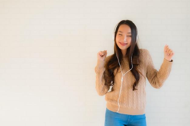 Retrato hermosa joven asiática feliz disfrutar con escuchar música Foto gratis
