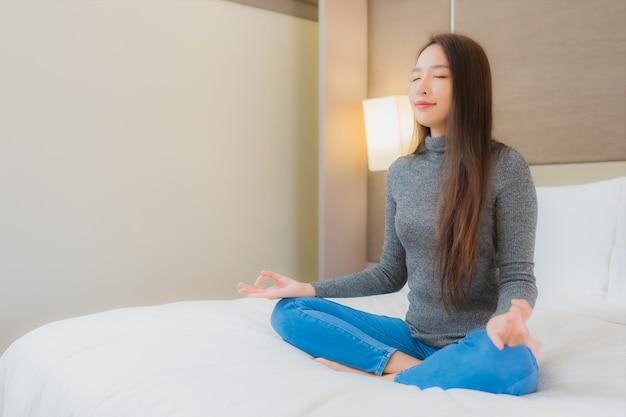Retrato de hermosa joven asiática haciendo meditación en la cama Foto gratis