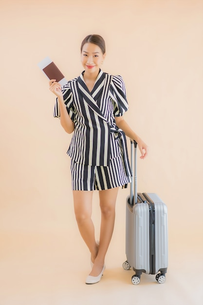Retrato hermosa joven asiática con pasaporte de bolsa de equipaje Foto gratis