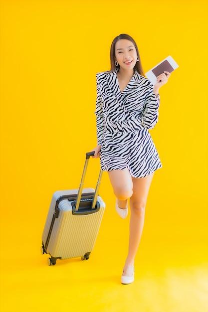 Retrato hermosa joven asiática con pasaporte de equipaje de viaje y tarjeta de embarque en amarillo Foto gratis