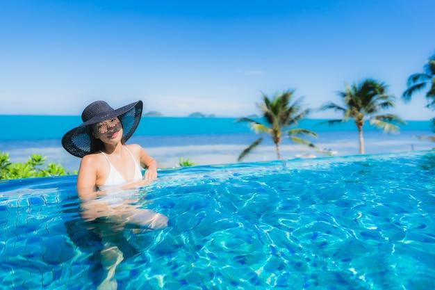 Retrato hermosa joven asiática relajarse en la piscina al aire libre de lujo en el hotel resort casi playa mar océano Foto gratis