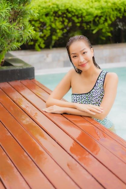 Retrato hermosa joven asiática relajarse sonrisa alrededor de la piscina al aire libre para el ocio y las vacaciones Foto gratis