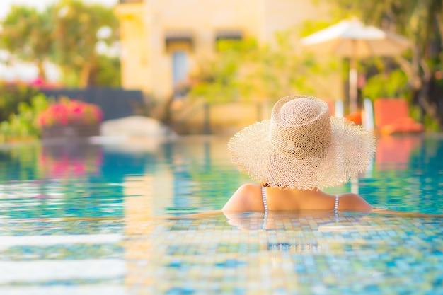 Retrato hermosa joven asiática relajarse sonrisa disfrutar de ocio alrededor de la piscina en el hotel resort de vacaciones Foto gratis