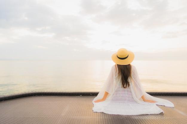 Retrato hermosa joven mujer asiática feliz sonrisa relajarse alrededor del mar playa océano Foto gratis