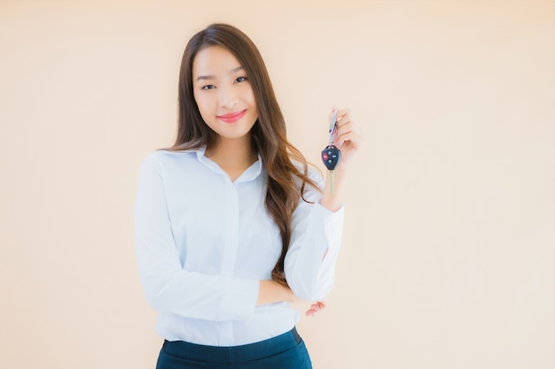 Retrato hermosa joven mujer asiática de negocios con llave de coche Foto gratis