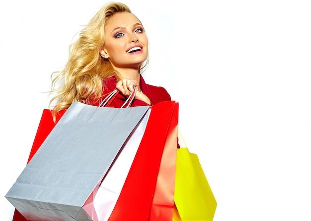 Retrato de hermosa linda feliz dulce sonriente rubia mujer niña sosteniendo en sus manos grandes bolsas de compras coloridas en hipster chaqueta roja aislado en blanco Foto gratis