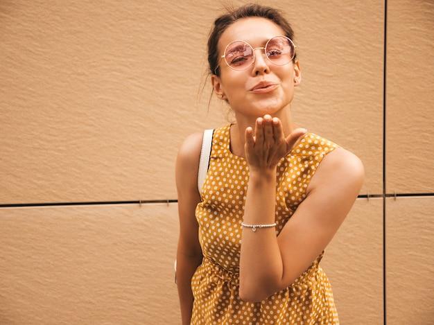 Retrato de la hermosa modelo hipster sonriente vestido con vestido amarillo de verano. chica de moda posando en la calle. mujer divertida y positiva que se divierte. beso de aire de gives Foto gratis