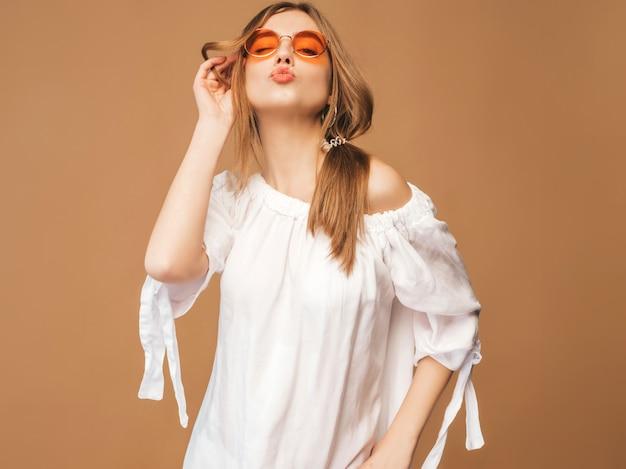Retrato de hermosa modelo lindo sonriente con labios rosados. chica en vestido blanco de verano. modelo posando en gafas de sol. dar beso Foto gratis