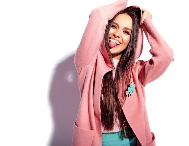 Retrato de la hermosa modelo de mujer morena caucásica sonriente en abrigo rosa brillante y elegante falda azul de verano aislado sobre fondo blanco Foto gratis