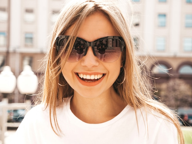 Retrato de la hermosa modelo rubia sonriente vestida con ropa hipster de verano. Foto gratis