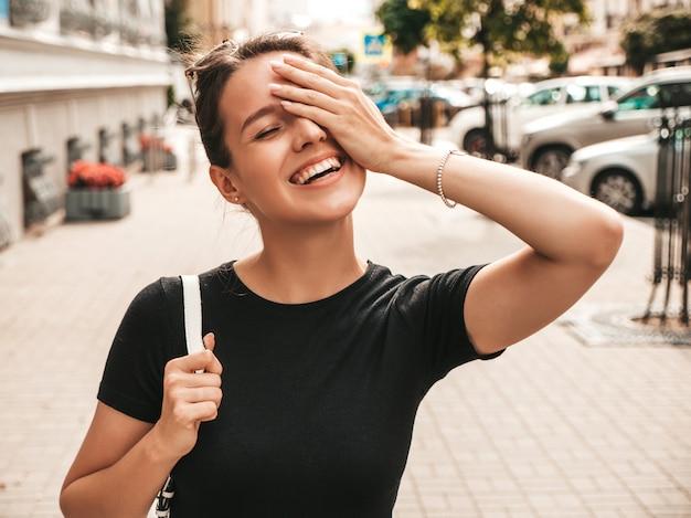 Retrato de hermosa modelo sonriente vestida con ropa de verano. chica de moda posando en la calle. mujer divertida y positiva divirtiéndose Foto gratis