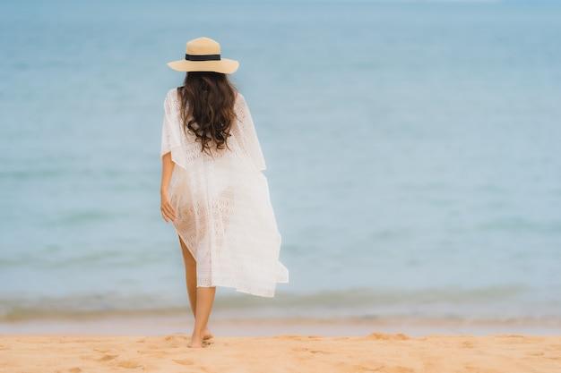 Retrato hermosa mujer asiática joven sonrisa feliz relajarse en la playa mar océano Foto gratis