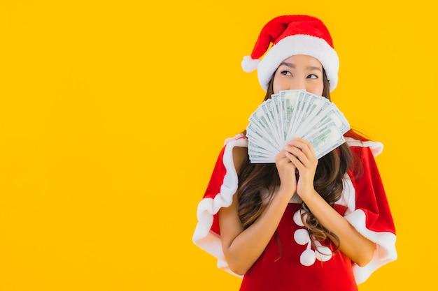 Retrato hermosa mujer asiática joven usar ropa de navidad y sombrero con dinero en efectivo Foto gratis