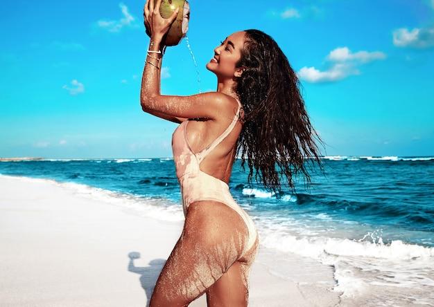 Retrato de hermosa mujer caucásica tomar el sol modelo con cabello largo y oscuro en traje de baño beige posando en la playa de verano con arena blanca en el cielo azul y el océano Foto gratis
