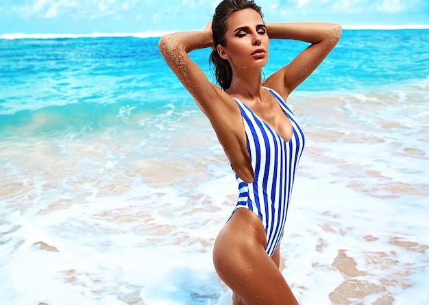 Retrato de hermosa mujer caucásica tomar el sol modelo con cabello largo y oscuro en traje de baño a rayas posando en la playa de verano con arena blanca Foto gratis