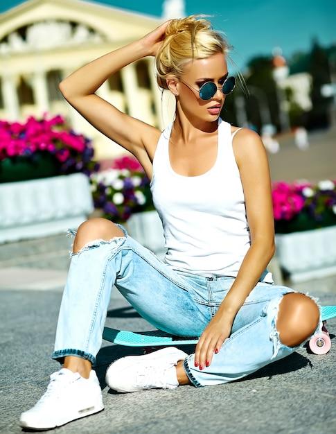 Retrato de hermosa mujer joven con estilo con patineta Foto gratis