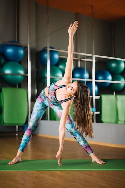 Retrato de hermosa mujer joven practicando yoga interior Foto gratis