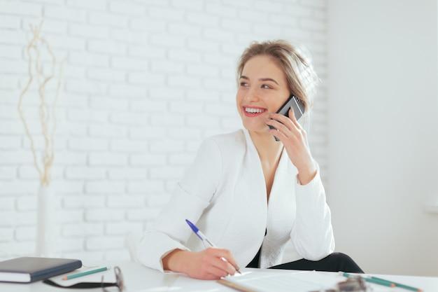 Retrato de hermosa mujer joven que trabaja en la oficina. Foto Premium