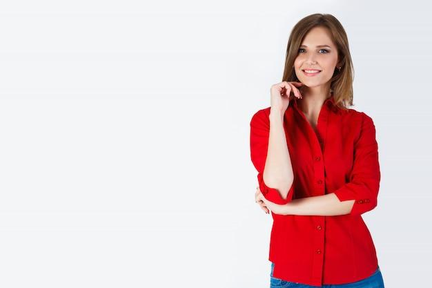 Retrato de hermosa mujer joven sonriente de pie en una camisa roja y jeans azul aislado Foto Premium