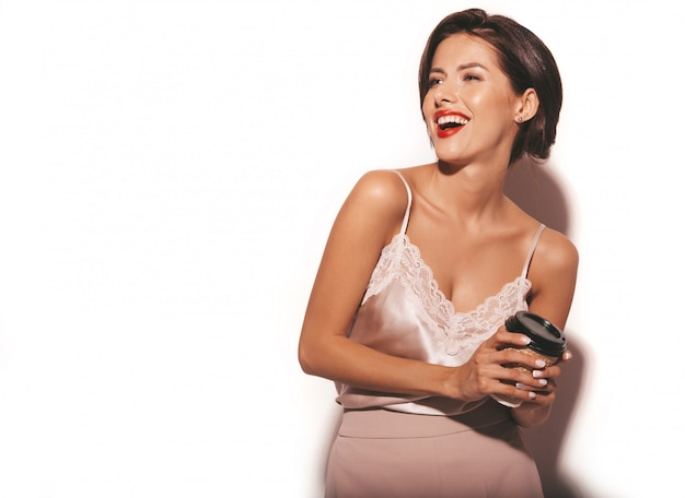 Retrato de hermosa mujer morena sensual. chica en ropa clásica beige elegante y pantalones anchos. modelo con taza de café de plástico Foto gratis