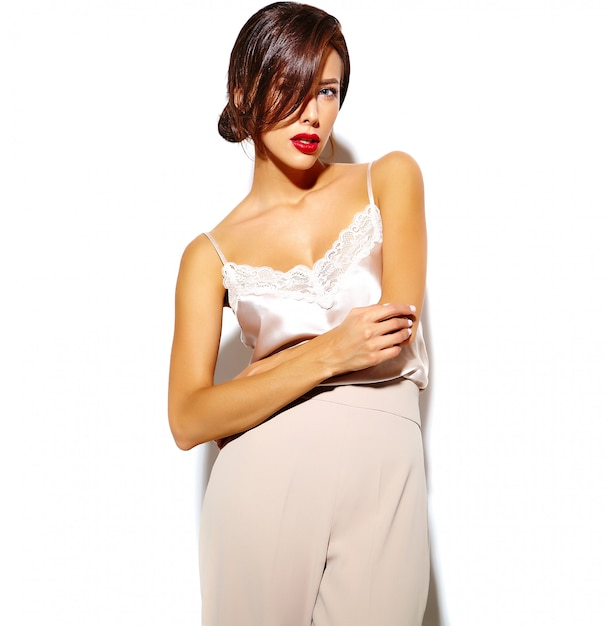 Retrato de hermosa mujer morena sexy linda feliz con labios rojos en amplios pantalones clásicos sobre fondo blanco. Foto gratis