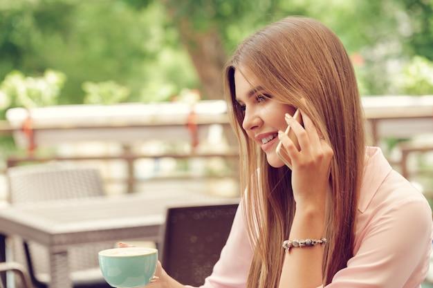 Retrato de hermosa niña usando su teléfono móvil en la cafetería Foto Premium