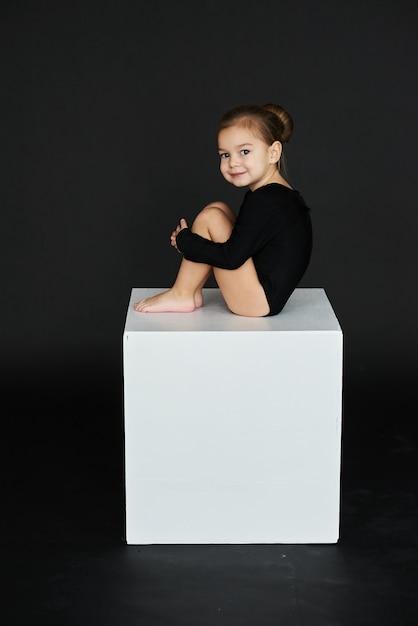 5c654360e Un retrato de una hermosa niña vestida con medias negras sobre un cubo  blanco sobre un fondo oscuro.