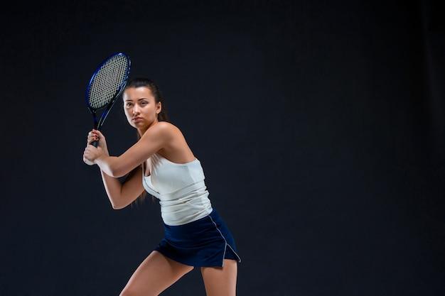 Retrato de la hermosa tenista con una raqueta en la pared oscura Foto gratis