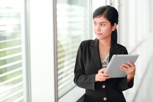 Retrato hermoso de la empresaria usando la tableta Foto Premium