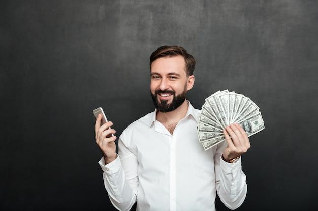 Retrato de hombre alegre en camisa blanca ganando mucho dinero en dólares usando su teléfono inteligente, siendo alegre sobre gris oscuro Foto gratis