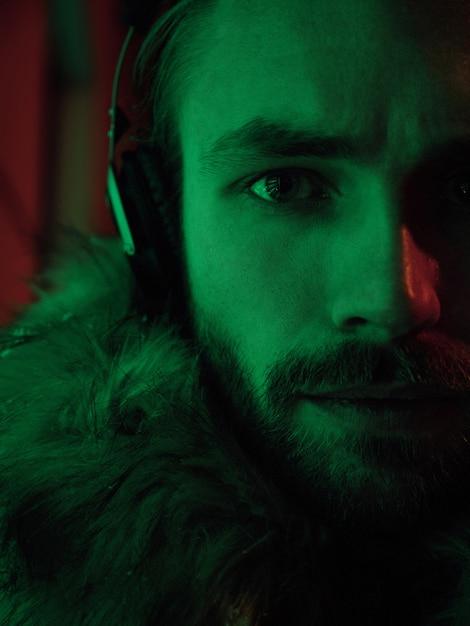 Retrato de hombre de arte neón moda modelo de chico guapo posando al aire libre y escuchando música en auriculares con filtros rojos y verdes. media cara Foto gratis
