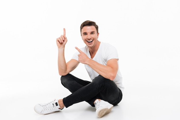 Retrato de un hombre atractivo feliz en camiseta blanca Foto gratis